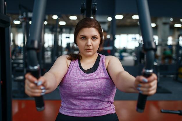 Übergewichtige frau auf übungsmaschine, draufsicht