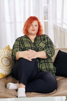 Übergewichtige frau, die auf sofa ruht