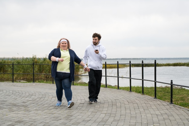 Übergewichtige frau, die draußen joggt