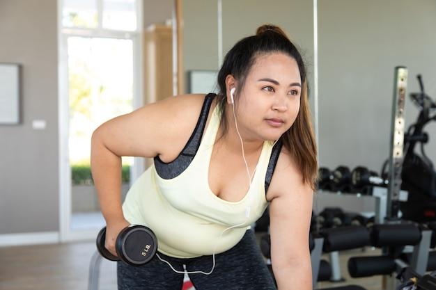 Übergewichtige frau, die ein fitness-training mit gewichten im fitnessstudio macht. gesunder lebensstil und sportkonzepte.
