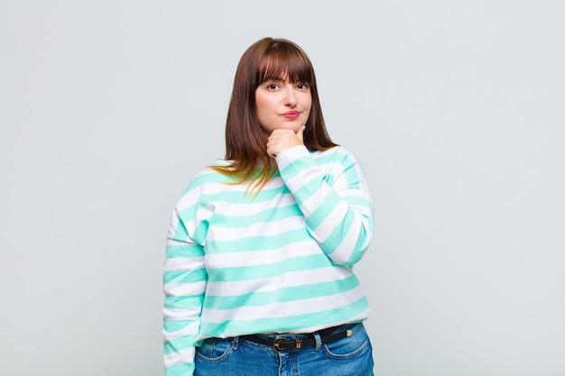 Übergewichtige frau, die ernst, verwirrt, unsicher und nachdenklich aussieht und an optionen oder entscheidungen zweifelt
