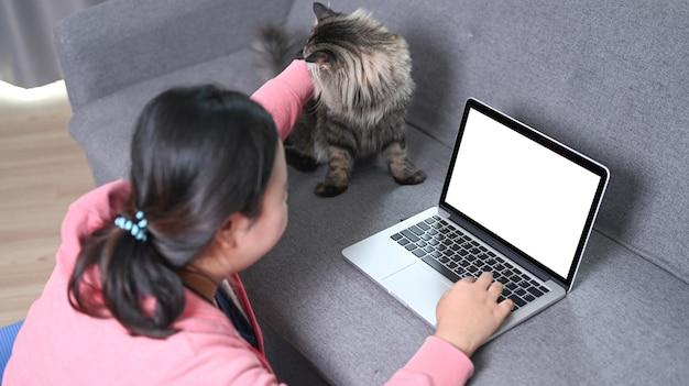 Übergewichtige frau, die laptop auf dem sofa benutzt und ihre reizende katze streichelt.