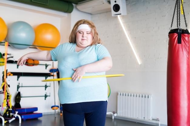 Übergewichtige frau, die mit hula hoop ausarbeitet