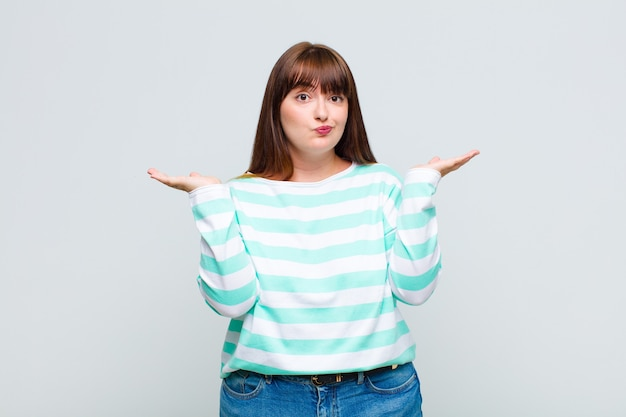 Übergewichtige frau, die sich verwirrt und verwirrt fühlt, zweifelt, gewichtet oder verschiedene optionen mit lustigem ausdruck wählt