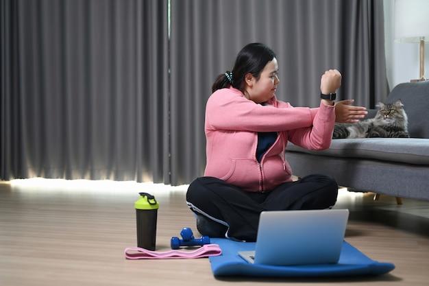 Übergewichtige frau, die vor übungen zu hause die arme ausdehnt.