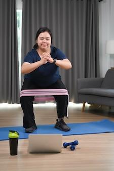 Übergewichtige frau, die zu hause mit fitness-gummiband trainiert. gewichtsverlust und gesunder lebensstil.