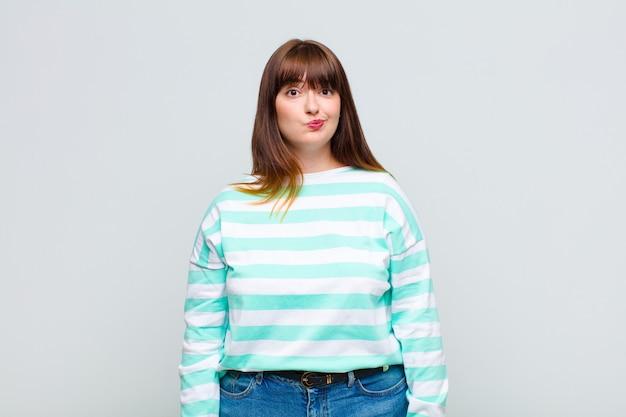 Übergewichtige frau fühlt sich verwirrt und zweifelhaft, wundert sich oder versucht zu wählen oder eine entscheidung zu treffen