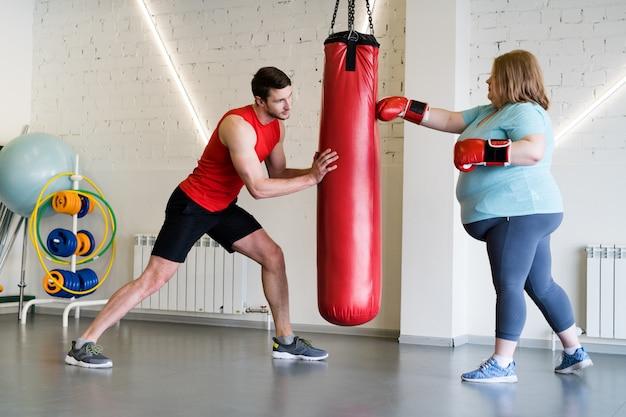 Übergewichtige frau im boxtraining