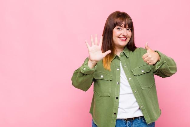 Übergewichtige frau lächelt und sieht freundlich aus, zeigt nummer sechs oder sechste mit der hand nach vorne und zählt herunter