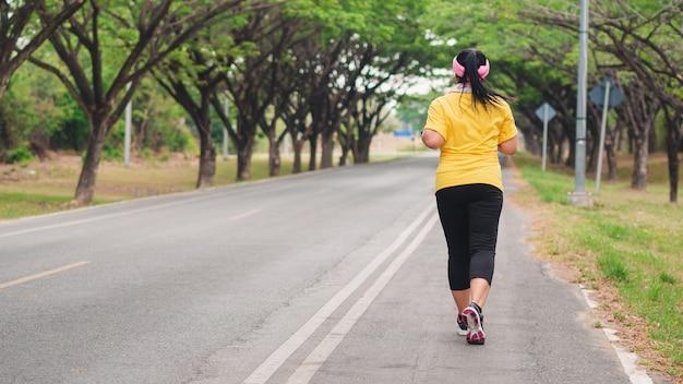 Übergewichtige frau läuft im park. gewichtsverlust konzept