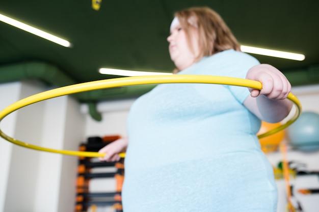 Übergewichtige frau mit hula hoop