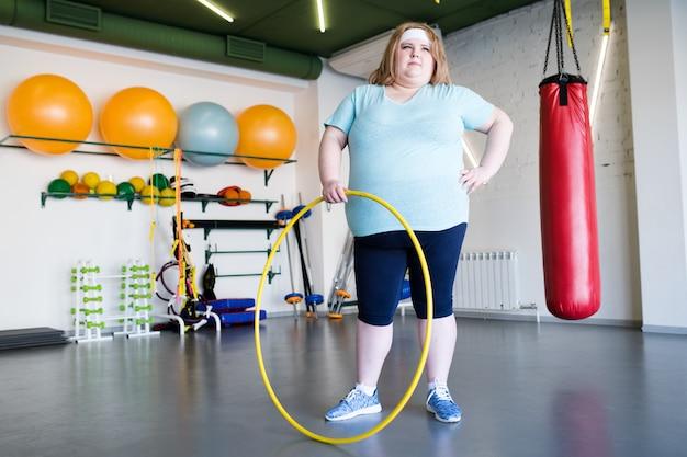 Übergewichtige frau posiert mit hula hoop