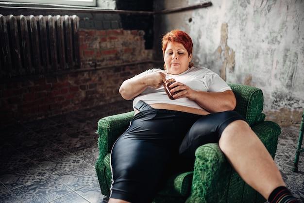 Übergewichtige frau sitzt auf einem stuhl und isst süßigkeiten. ungesunder lebensstil, fettleibigkeit