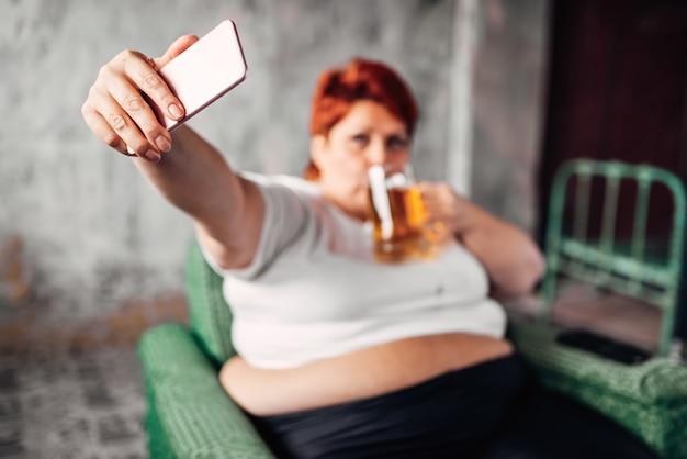 Übergewichtige frau trinkt bier und macht selfie, faulheit und fettleibigkeit. ungesunder lebensstil, fette frau