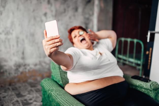 Übergewichtige frau trinkt bier und macht selfie