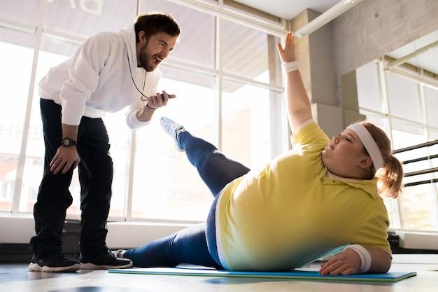Übergewichtige junge frau, die mit trainer ausarbeitet