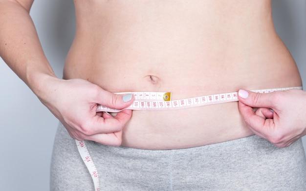 Übergewichtige oder fette erwachsene frau misst am zwerchfell um den körper herum. gesundheitswesen, medizin-konzept.