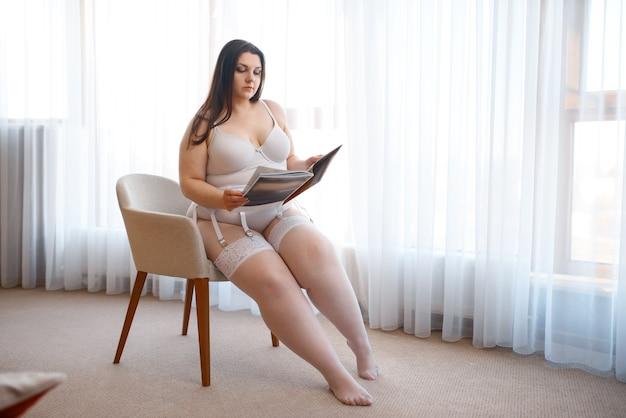 Übergewichtige verdorbene frau mit magazin posiert im sessel in erotischen dessous.