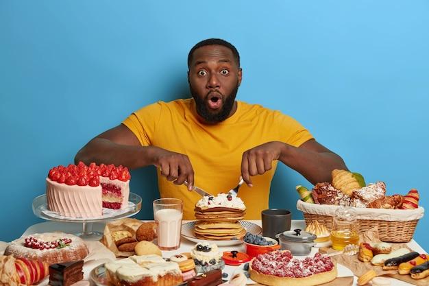Übergewichtiger bärtiger junger mann hat dunkle haut, überrascht von völlerei, isst leckere cremige pfannkuchen und andere desserts, hat einen ungesunden lebensstil