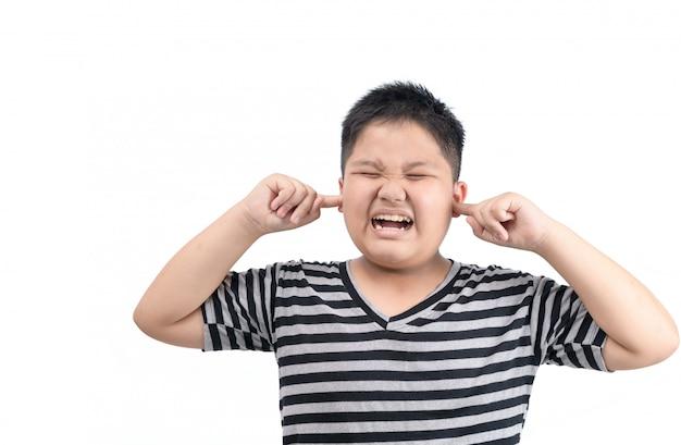 Übergewichtiger dicker junge, der ohren bedeckt und störendes lautes geräusch isoliert ignoriert
