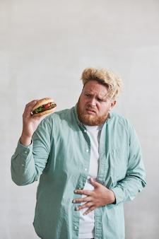 Übergewichtiger junger mann, der sich burger in der hand anschaut und bauchschmerzen von fast food hat, isoliert...