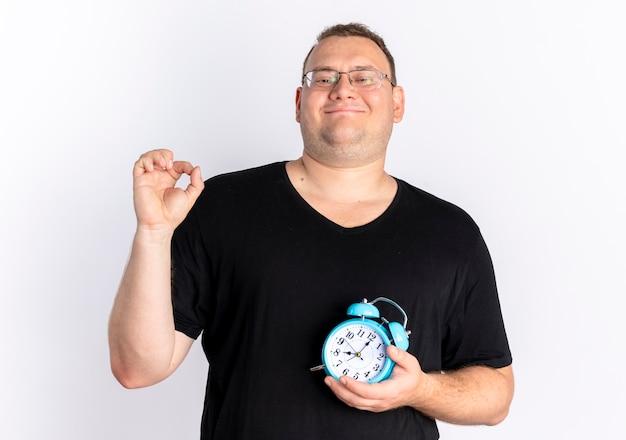 Übergewichtiger mann, der schwarzes t-shirt in den gläsern hält, die wecker halten, der mit glücklichem gesicht über weißer wand steht