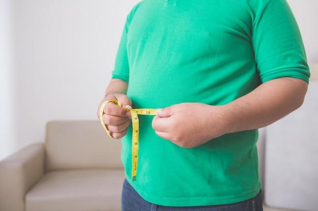 Übergewichtiger mann, der zu hause seinen bauch misst