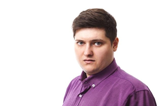 Übergewichtiger mann im lila wohltätigkeitshemd, das kamera auf weiß betrachtet