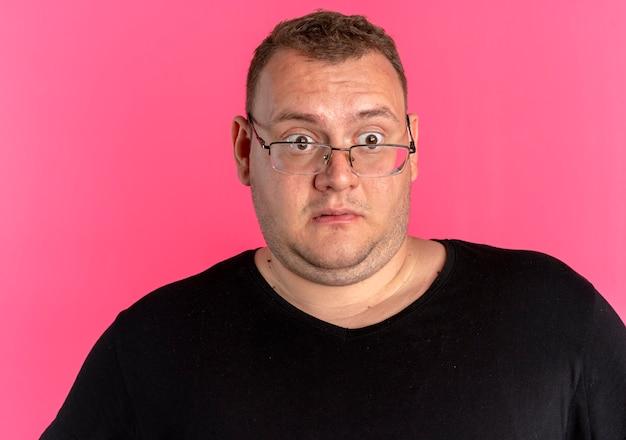 Übergewichtiger mann in brille, der schwarzes t-shirt trägt, das überrascht und erstaunt beiseite schaut, das über rosa wand steht