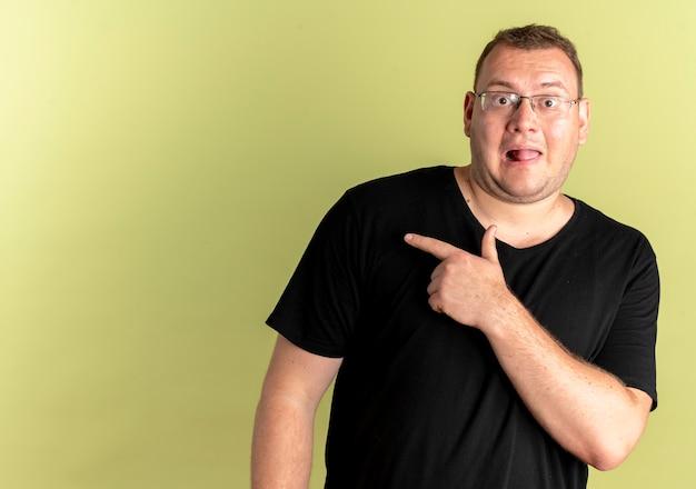 Übergewichtiger mann in brille trägt schwarzes t-shirt glücklich und überrascht, mit dem finger zur seite stehend über der hellen wand stehend
