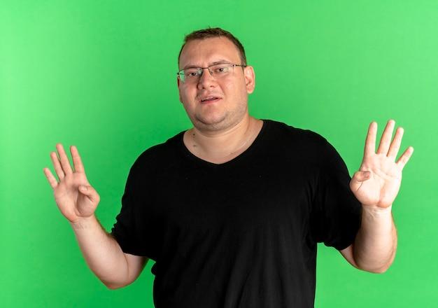 Übergewichtiger mann in brille trägt schwarzes t-shirt und zeigt mit den fingern nummer acht über grün