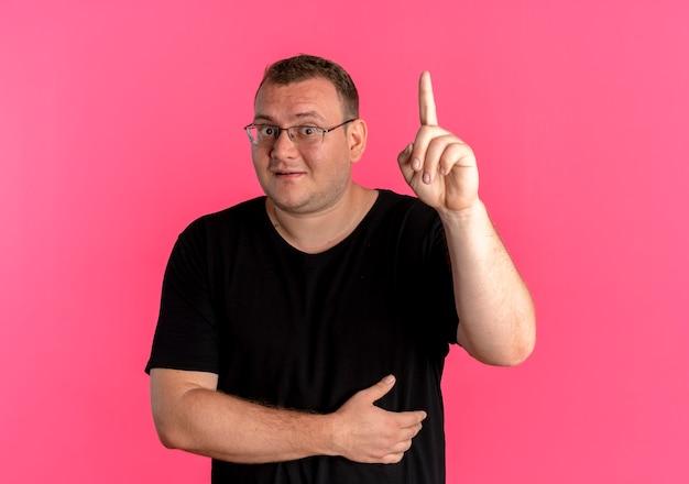 Übergewichtiger mann in der brille, die das lächelnde schwarze t-shirt zeigt, das zeigefinger zeigt, der neue große idee hat, die über rosa wand steht