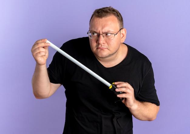 Übergewichtiger mann in der brille, die das schwarze t-shirt hält, das das lineal hält, das beiseite schaut wie ein spion, der über der blauen wand steht