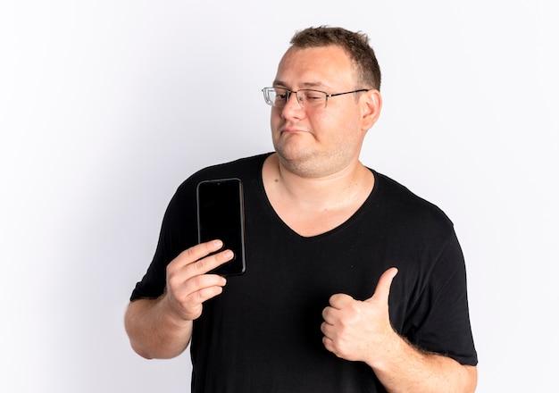 Übergewichtiger mann in der brille, die das schwarze t-shirt hält, das smartphone hält, das daumen oben zeigt, die über weißer wand stehen