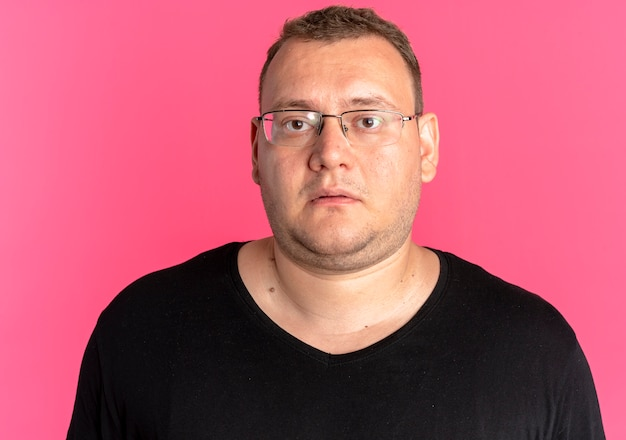 Übergewichtiger mann in der brille, die das schwarze t-shirt trägt, das kamera mit traurigem ausdruck betrachtet, der über rosa wand steht