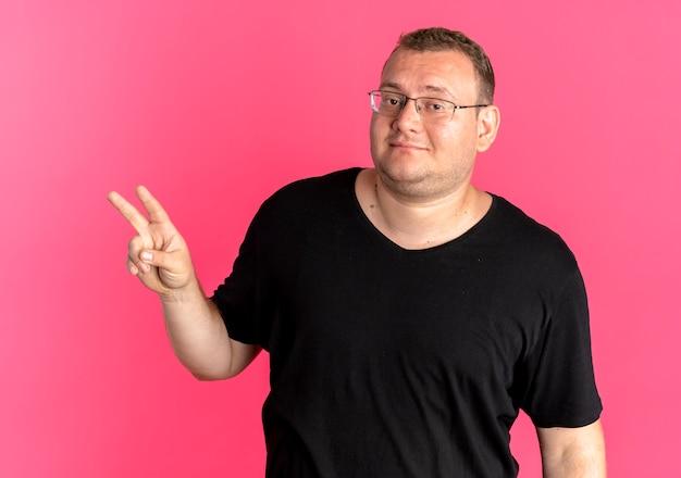 Übergewichtiger mann in der brille, die schwarze t-shirts mit nummer zwei oder siegeszeichen trägt, die über rosa lächeln