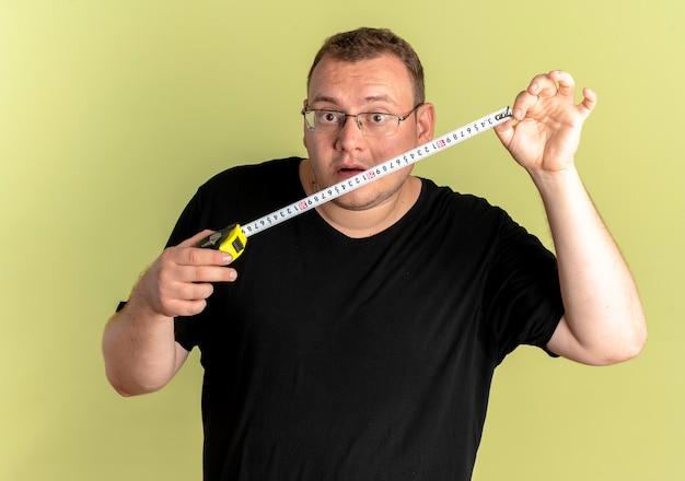 Übergewichtiger mann in der brille, die schwarzes t-shirt hält, das lineal hält, das es über licht überrascht betrachtet