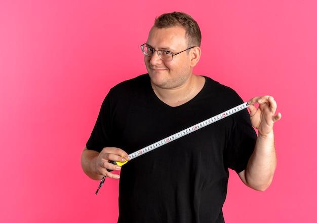 Übergewichtiger mann in der brille, die schwarzes t-shirt hält, das lineal mit glücklichem gesicht über rosa hält