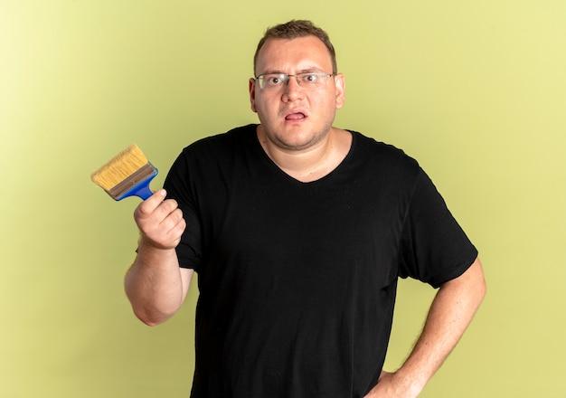Übergewichtiger mann in der brille, die schwarzes t-shirt hält, das pinsel hält, wie fragend oder streitend steht über heller wand