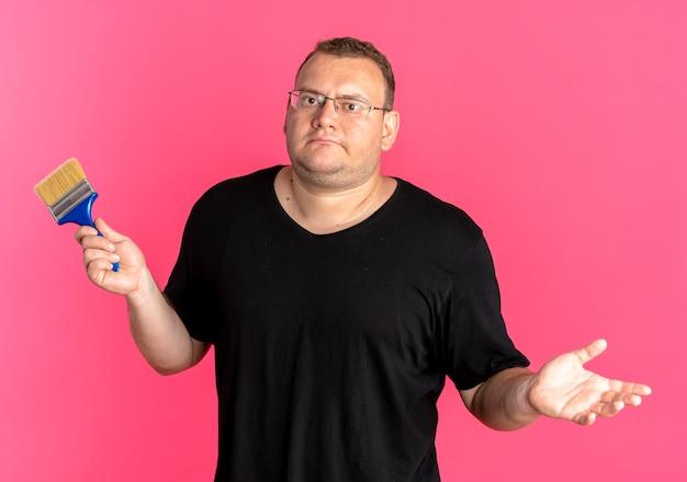 Übergewichtiger mann in der brille, die schwarzes t-shirt hält, das pinsel spreizt, der arm zur seite spreizt, verwirrt über rosa schaut