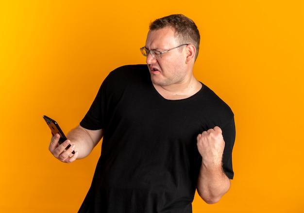 Übergewichtiger mann in der brille, die schwarzes t-shirt hält, das smartphone geballte faust mit aggressivem ausdruck über orange hält