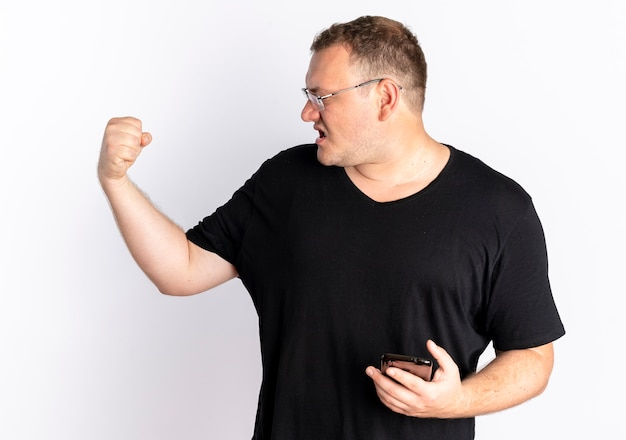 Übergewichtiger mann in der brille, die schwarzes t-shirt hält, das smartphone geballte faust mit wütendem gesicht hält, das über weißer wand steht