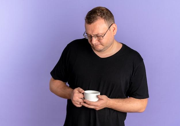 Übergewichtiger mann in der brille, die schwarzes t-shirt hält kaffeetasse hält, die es mit nachdenklichem ausdruck über blau betrachtet