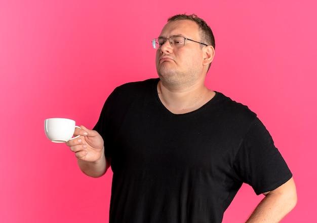 Übergewichtiger mann in der brille, die schwarzes t-shirt hält kaffeetasse hält, die über rosa selbstzufrieden aussieht