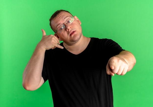 Übergewichtiger mann in der brille, die schwarzes t-shirt macht, ruft mich geste, die mit zeigefinger zeigt, der über grüner wand steht