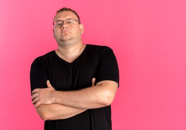 Übergewichtiger mann in der brille, die schwarzes t-shirt mit serösem gesicht mit verschränkten armen auf brust trägt, die über rosa wand stehen
