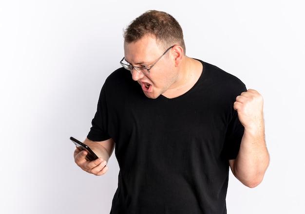Übergewichtiger mann in der brille, die schwarzes t-shirt trägt, das bildschirm seiner geballten faust des smartphones mit wütendem gesicht betrachtet, das über weißer wand steht