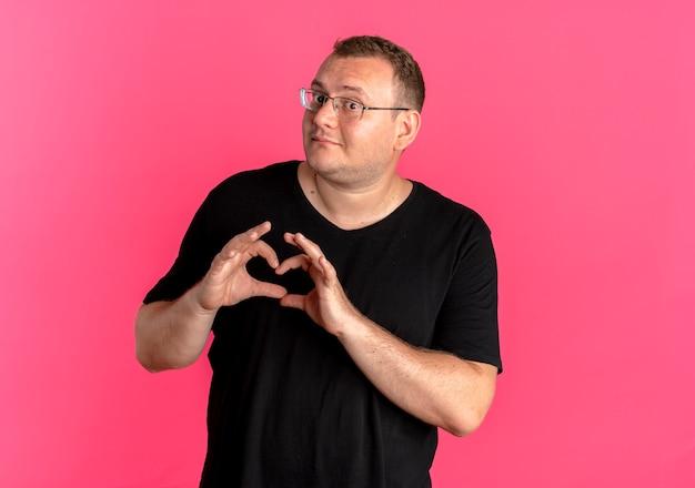 Übergewichtiger mann in der brille, die schwarzes t-shirt trägt, das herzgeste mit den lächelnden fingern macht, die über rosa wand stehen