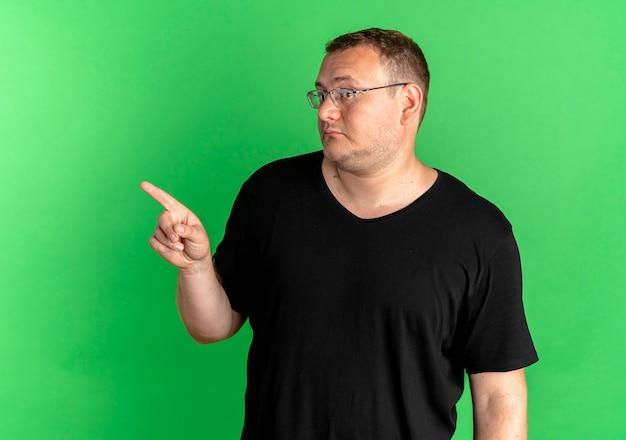 Übergewichtiger mann in der brille, die schwarzes t-shirt trägt, das mit dem finger zur seite zeigt, verwirrt über grün schaut