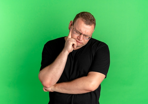 Übergewichtiger mann in der brille, die schwarzes t-shirt trägt, das mit nachdenklichem ausdruck auf gesicht über grün beiseite schaut